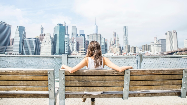 girl sitting on a bench looking at skyline