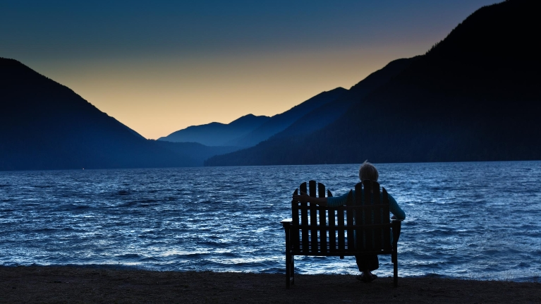 Person sitting at ocean alone