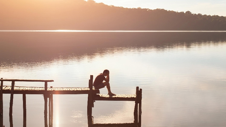 Person sitting alone at water with head in hands