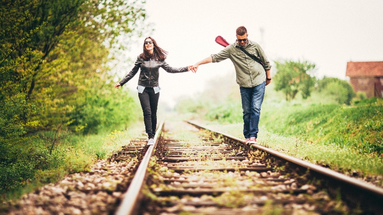 Couple walking on railroad tracks