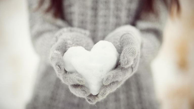 Girl holding heart shaped snowball