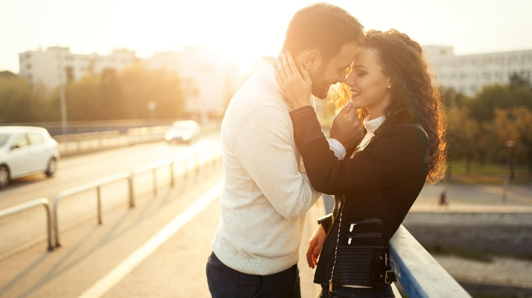 couple kissing on side of road