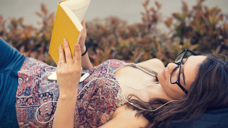 girl laying in grass reading and listening to podcast