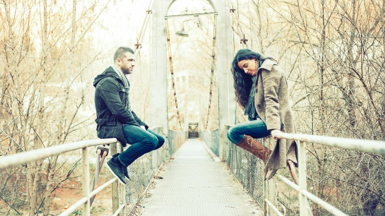 Girl and guy on a bridge look at eachother